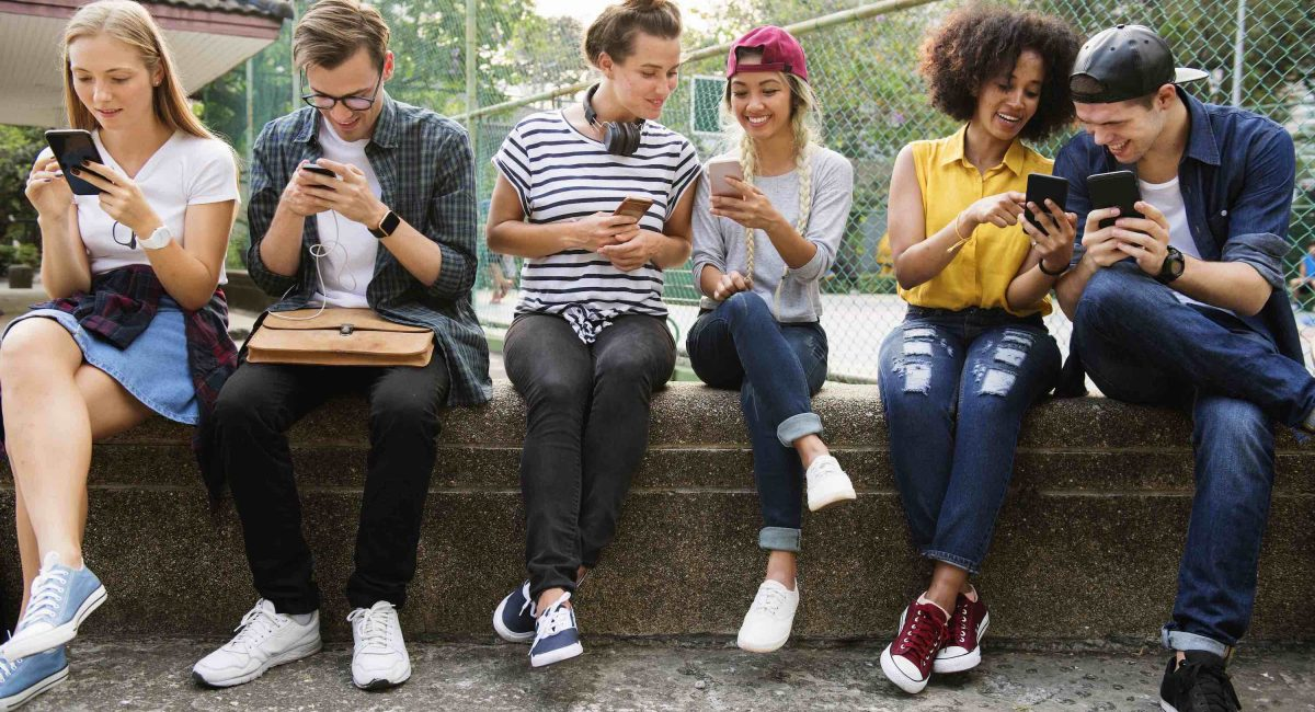 young-adult-friends-using-smartphones-together-Z7TBUHY